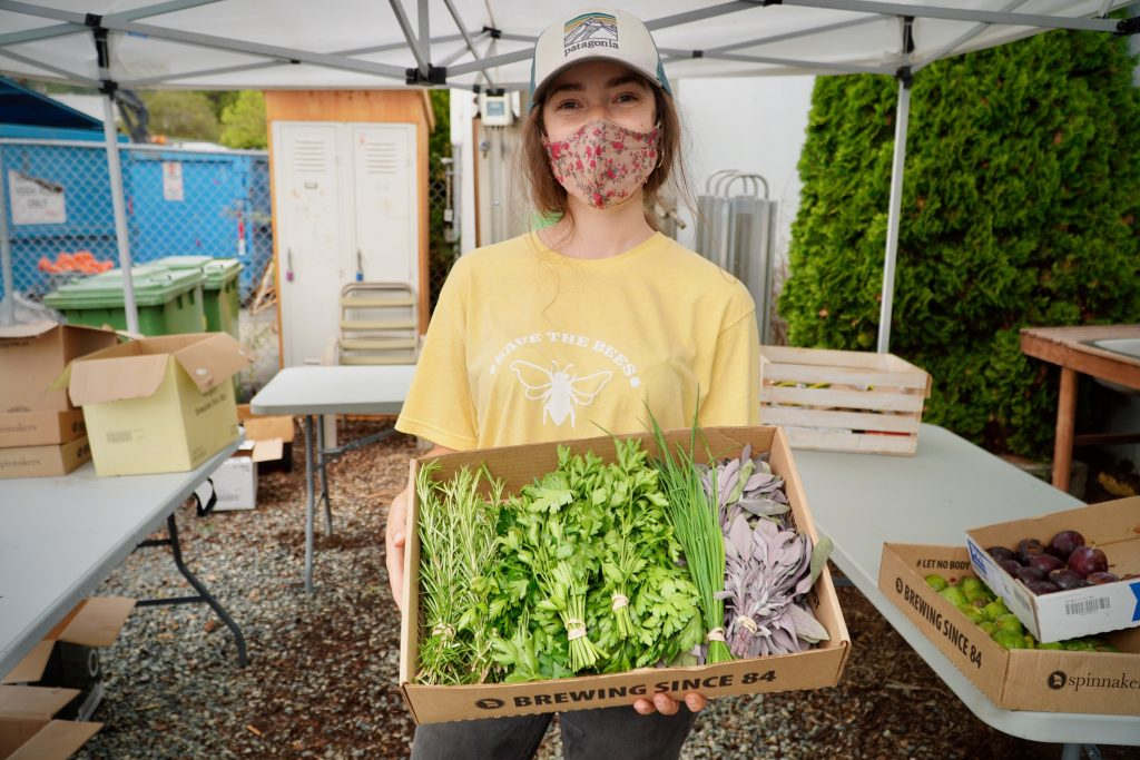 Smiling woman wearing a mask and holding a box filled with greens.